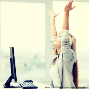 Cheering woman at desk | Tami McVay - Wellness & Lifestyle Coach